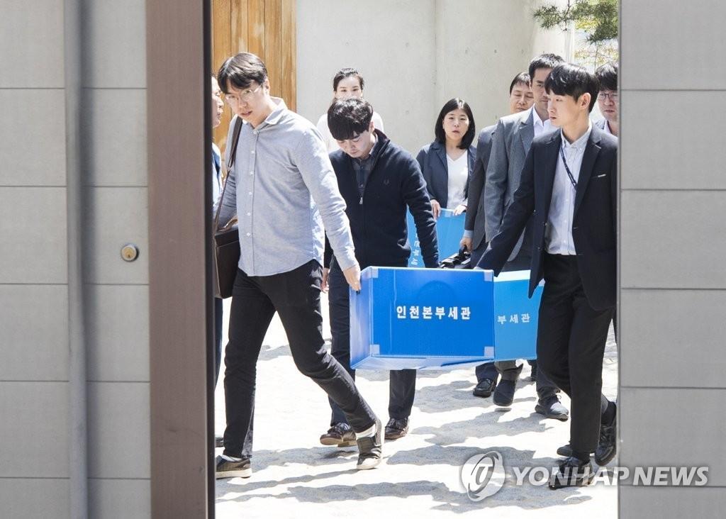 资料图片:4月21日下午,海关人员在搜查韩进集团总裁三子女私宅后,带着物品离开。(韩联社)