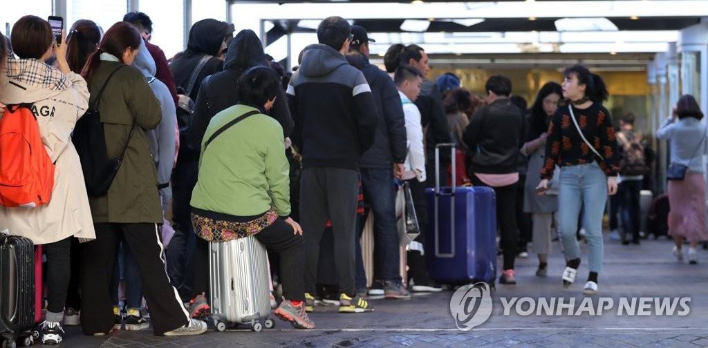 4月24日上午,在首尔某免税店前,外籍顾客排队等待开门。(韩联社)