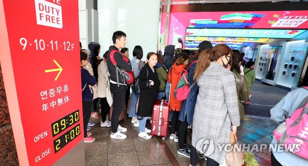 资料图片:4月24日上午,一批外国游客在首尔一家免税店等待开门。(韩联社)