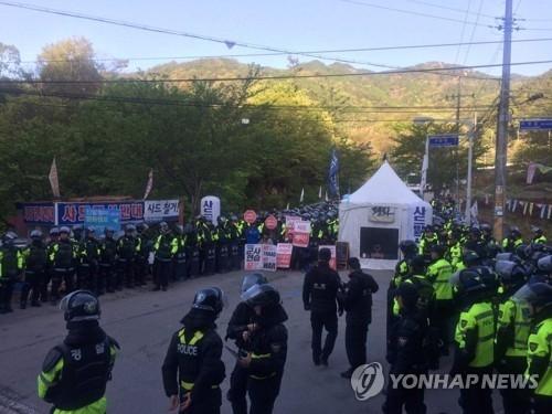 4月25日,在庆尚北道星州郡,8名反对国防部将建材运进萨德基地的居民遭警方强制驱散。(韩联社)