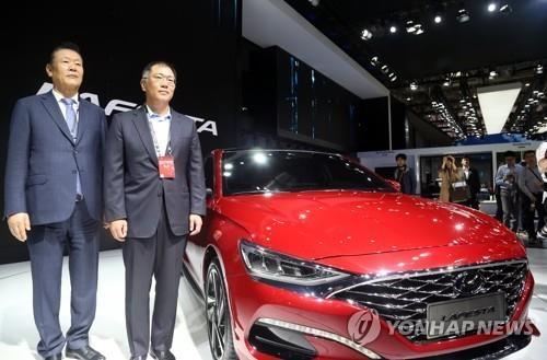 现代汽车副会长郑义宣(右)与现代新车Lafesta合影。(韩联社)