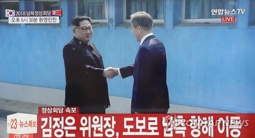4月27日,在韩朝边境板门店,韩国总统文在寅(右)同朝鲜国务委员会委员长金正恩会晤并握手。(韩联社/韩联社TV截图)