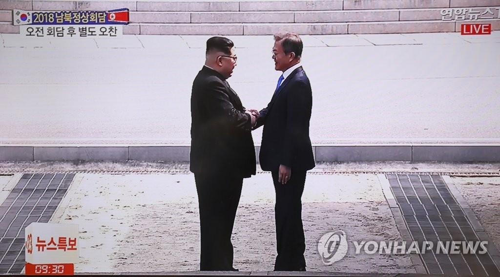 4月27日,在韩朝边境板门店,韩国总统文在寅(右)同朝鲜国务委员会委员长金正恩握手。(韩联社/韩联社TV截图)