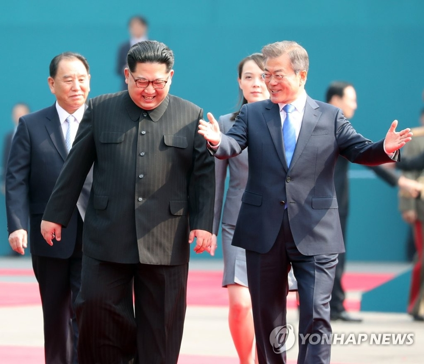 4月27日,在韩朝边境板门店,韩国总统文在寅(右)同朝鲜国务委员会委员长金正恩共同走向会场。(韩联社)