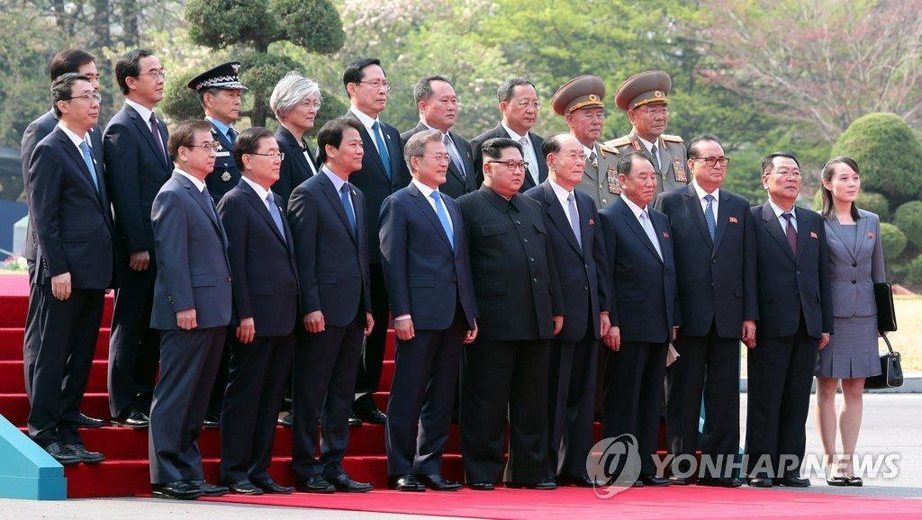4月27日,在板门店,韩国总统文在寅(前排左四)和朝鲜国务委员会委员长金正恩(前排左五)同双方随行人员合影留念。(韩联社)