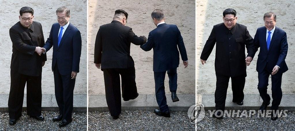 4月27日上午,在板门店,文在寅和金正恩从军事分界线南侧牵手向北迈步跨线后又回到南侧。(韩联社)