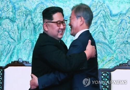 4月27日,在板门店,文在寅(右)与金正恩在签署《板门店宣言》后拥抱致意。(韩联社)