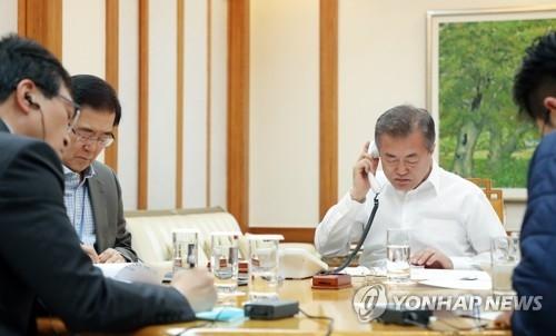 4月28日晚,在青瓦台,韩国总统文在寅正在与美国总统特朗普通电话。(韩联社/青瓦台提供)