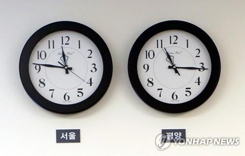 """资料图片:举行文金会的""""和平之家""""一楼接待室的墙上曾挂着显示首尔时间(左)和平壤时间的两个时钟。(韩联社)"""
