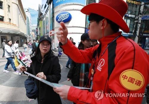 资料图片:4月13日,在首尔明洞街头,中国游客向导游问路。(韩联社)