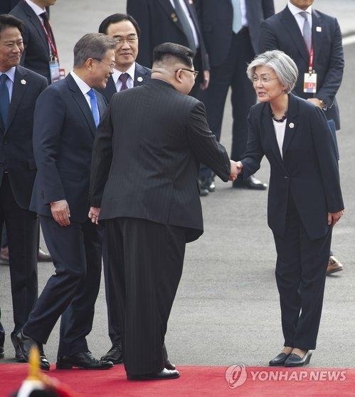 4月27日,在韩朝边境板门店,康京和(右)在欢迎仪式上与金正恩握手交谈。(韩联社)