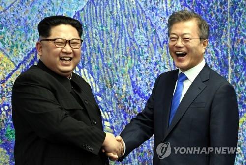 4月27日,在韩朝边境板门店,韩国总统文在寅(右)同朝鲜国务委员会委员长金正恩在举行会谈前欢笑握手。(韩联社)