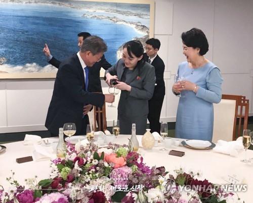 """4月27日,在板门店韩方一侧的""""和平之家"""",朝鲜劳动党中央委员会第一副部长金与正(左二)为韩国总统文在寅(左)、第一夫人金正淑倒酒。韩国总统府29日发布了一大波韩朝首脑会谈花絮照片。(韩联社/青瓦台官方脸谱)"""