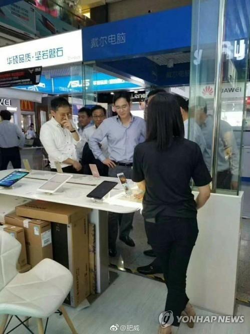 5月3日,在深圳小米之家,三星电子副会长李在镕在三星手机展台参观。(韩联社/微博截图)