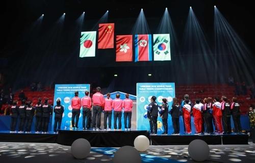 5月6日,在瑞典哈尔姆斯塔德举行的2018年世界乒乓球团体锦标赛特别颁奖仪式上,韩朝女乒联队队员一同仰望韩国和朝鲜国旗并排升起。(韩联社/大韩乒乓球协会提供)