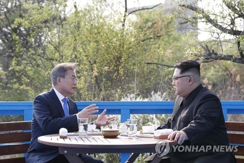 资料图片:4月27日,在板门店,文在寅(左)与金正恩交谈。(韩联社)