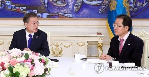 资料图片:3月7日,在青瓦台,文在寅(左)邀请朝野五党领袖共进午餐。右为自由韩国党代表洪准杓。(韩联社)