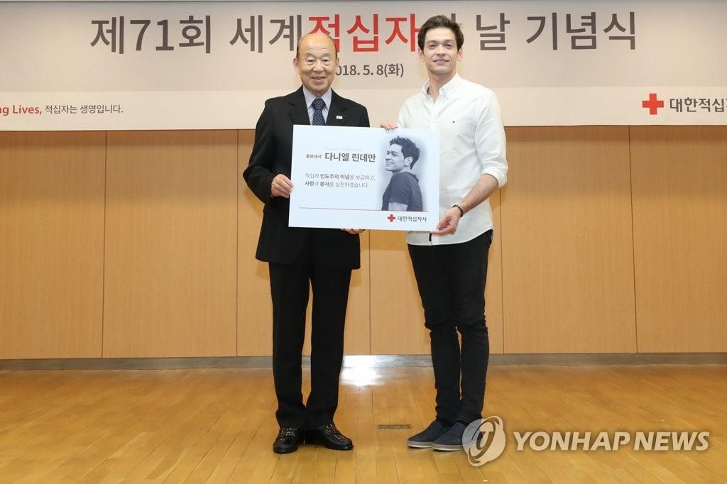 5月8日,在首尔大韩红十字会总部,大韩红十字会会长朴庚绪(左)和宣传大使丹尼尔·林德曼合影留念。(韩联社)