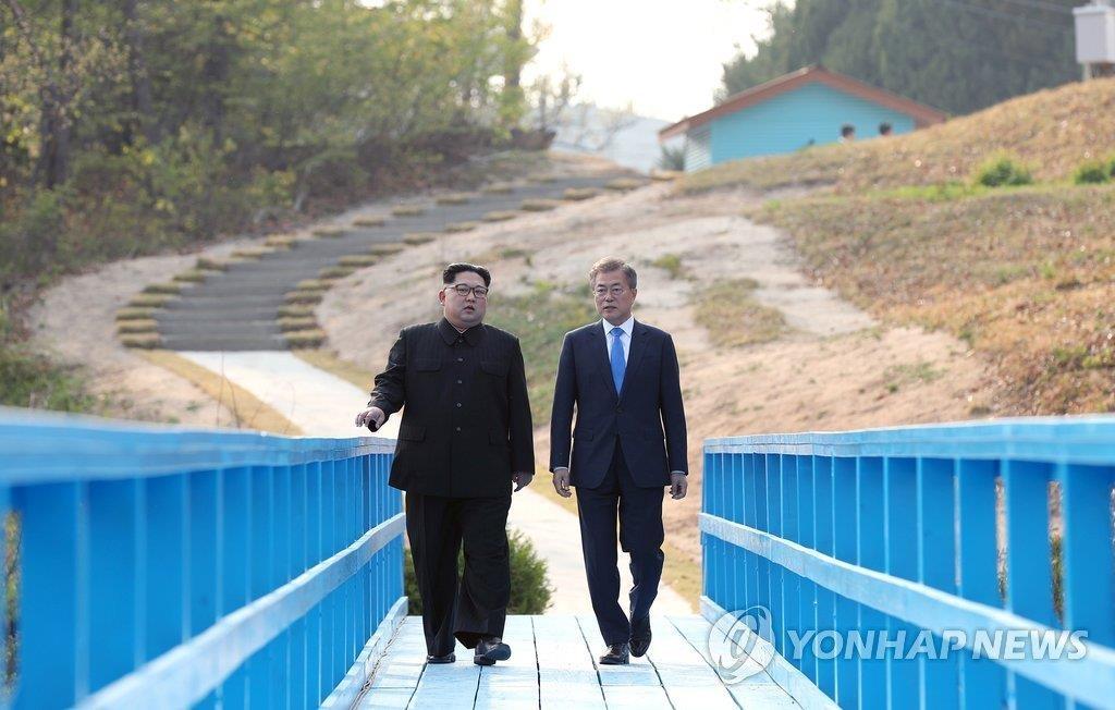 资料图片:4月27日,在板门店步行桥,韩国总统文在寅(右)和朝鲜国务委员会委员长金正恩正在散步。(韩联社)