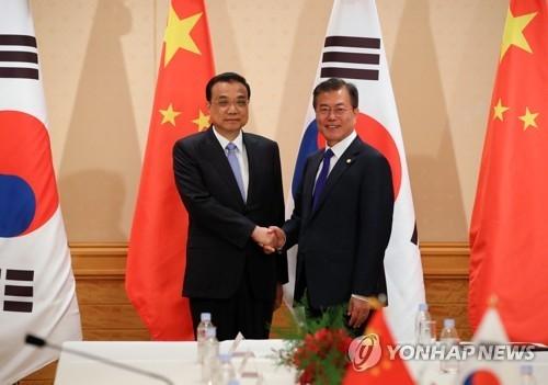 5月9日,在日本东京,为出席第七次韩中日领导人会议访问日本的韩国总统文在寅(右)同中国国务院总理李克强举行双边会谈。(韩联社)