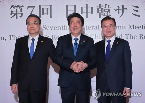 5月9日,韩中日领导人会议在东京举行,图为李克强(左起)、安倍晋三和文在寅牵手合影。(韩联社)