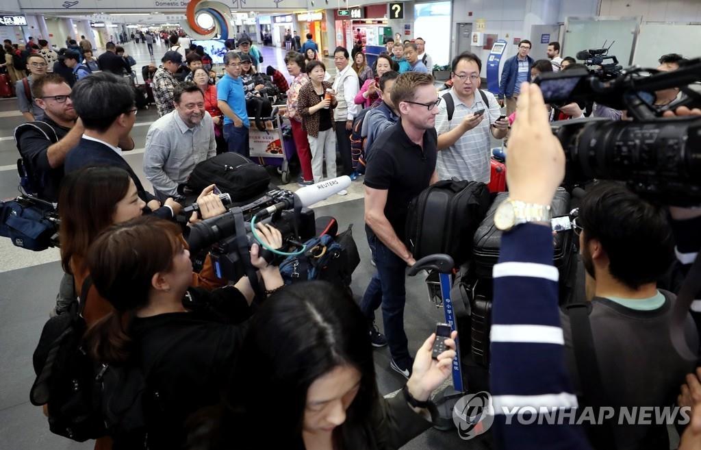 5月22日上午,在北京首都机场,获邀见证拆除丰溪里核试验场的外媒记者们正准备搭乘高丽航空包机赴朝。(韩联社)
