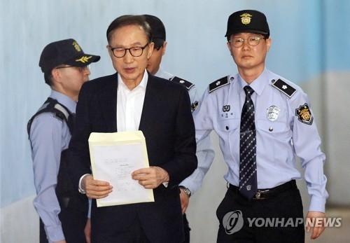 5月23日下午,在首尔中央地方法院,李明博走向法庭。(韩联社)