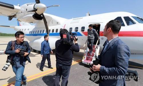 5月23日下午,采访朝鲜丰溪里核试验场废弃仪式的韩国记者团飞抵朝鲜江原道元山市葛麻机场,从政府运输机下机。(韩联社/联合采访团)