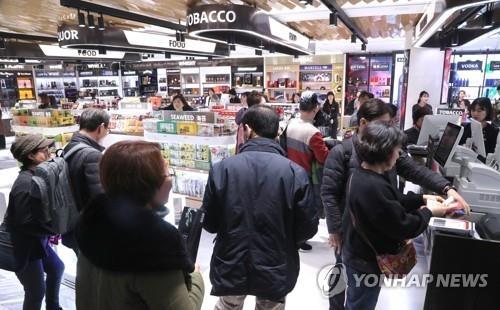 资料图片:在免税店购物的中国游客(韩联社)