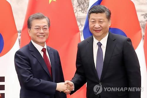资料图片:2017年12月14日下午,在北京人民大会堂,韩国总统文在寅(左)和中国国家主席习近平握手合影。(韩联社)