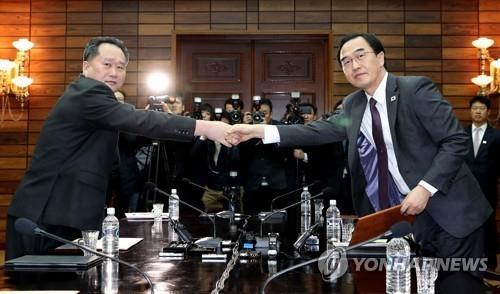 资料图片:3月29日上午,在韩朝边境板门店朝方一侧的统一阁,赵明均(右)和李善权交换联合新闻稿,并握手合影。(韩联社)