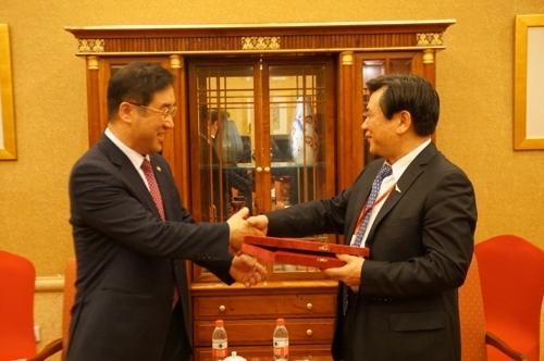 资料图片:1月30日,在北京,韩国国土交通部第二次官(副部长)孟圣奎(左)同中国民用航空局局长就韩中主要航空问题进行磋商后亲切握手。(韩联社/韩国国土交通部提供)