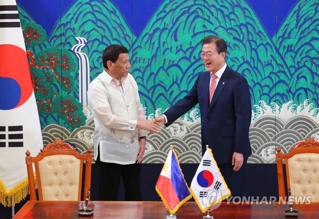 6月4日下午,在韩国总统府青瓦台,总统文在寅(右)和菲律宾总统罗德里戈·杜特尔特在首脑会谈结束后签署谅解备忘录并握手合影。(韩联社)