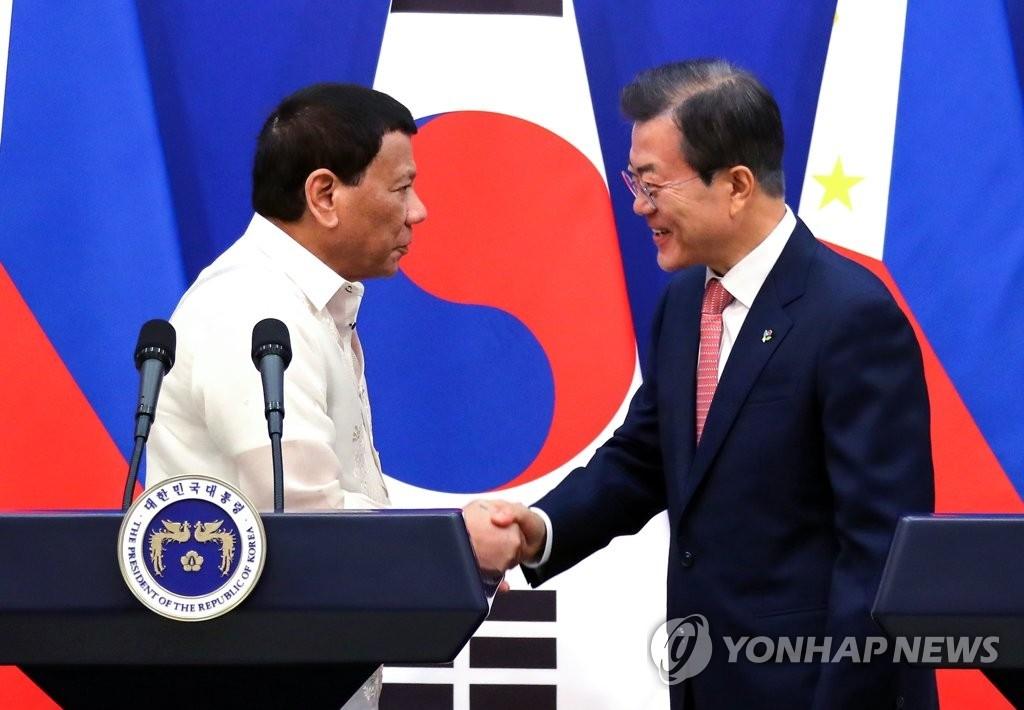 6月4日下午,在韩国总统府青瓦台,总统文在寅(右)和菲律宾总统罗德里戈·杜特尔特在发表联合声明后握手致意。(韩联社)