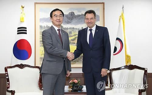 6月5日上午,在中央政府首尔办公大楼,赵明均(左)与毛雷尔在会谈前握手合影。(韩联社)