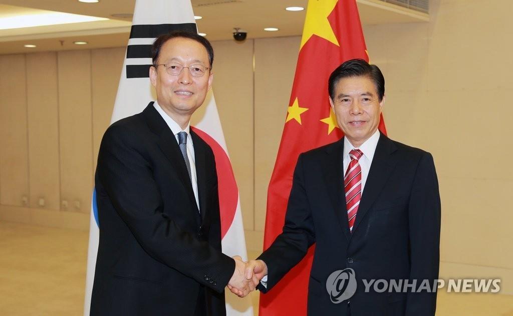 6月5日,在北京,韩国产业通商资源部长官白云揆(左)同中国商务部部长钟山在会前握手合影。(韩联社/产业部提供)