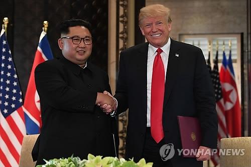 资料图片:6月12日,在新加坡,朝鲜国务委员会委员长金正恩(左)和美国总统特朗普共同签署联合声明后握手合影。(韩联社)
