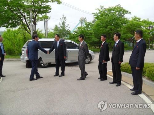 6月8日,在韩朝交流合作协议事务所前,韩朝共同联络事务所韩方考察团一行同朝方人士握手示意。(韩联社/统一部提供)