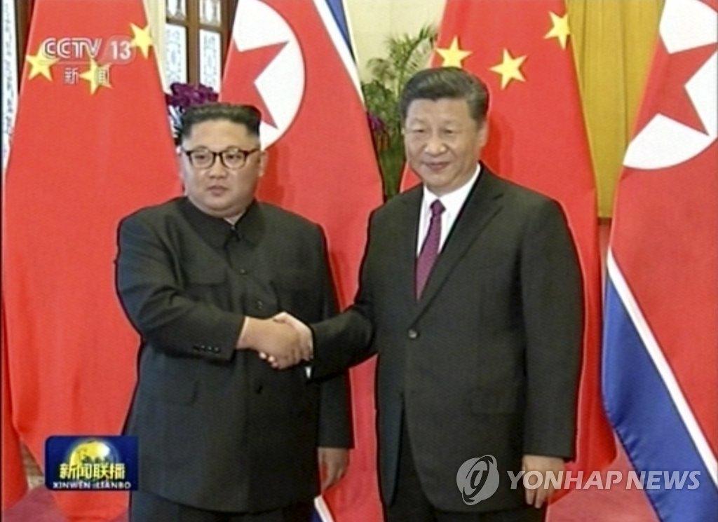 6月19日,朝鲜国务委员会委员长金正恩(左)在北京人民大会堂举行的欢迎仪式上同中国国家主席习近平握手合影。(韩联社/美联社/央视画面截图)