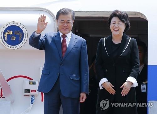 6月24日,结束对俄罗斯国事访问的韩国总统文在寅和夫人金正淑乘专机飞抵位于京畿道城南市的首尔机场,向接机人群挥手致意。(韩联社)