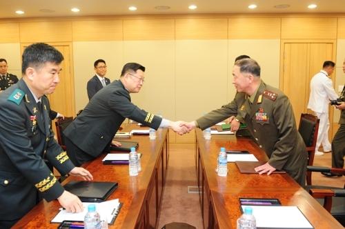 6月25日,韩朝在韩朝出入境事务所举行大校级工作会谈,图为会前双方代表握手。(韩联社/国防部提供)