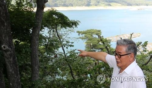 """图为韩中国际友好联络和平促进会会长许壮焕站在""""破虏湖""""边介绍历史。(韩联社)"""