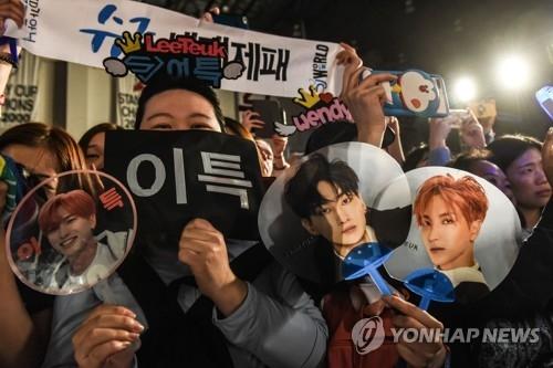 6月23日,在纽瓦克保诚中心,参加KCON纽约站的粉丝们拿着贴有SJ利特照片的扇子热烈欢呼。(韩联社)
