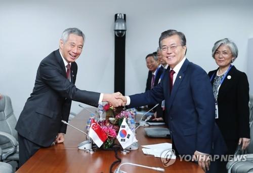 资料图片:2017年11月14日,在菲律宾,韩国总统文在寅(右二)与新加坡总理李显龙握手合影。(韩联社)