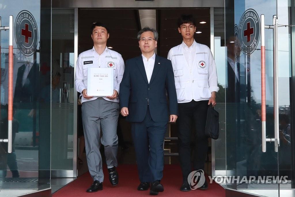 7月3日上午,在位于首尔中区的大韩红十字会首尔事务所,大韩红十字会国际南北局局长禹光浩(中)手持250名韩方离散家属的生死确认委托书启程前往板门店。(韩联社)