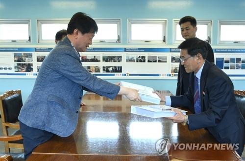 资料图片:7月3日下午,在板门店,韩朝交换双方的离散家属生死确认委托书。(韩联社)