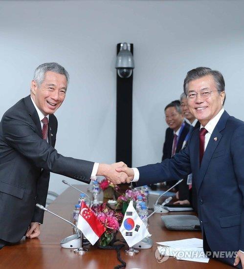 资料图片:当地时间2017年11月14日,在菲律宾马尼拉,韩国总统文在寅(右)与新加坡总理李显龙在双边会谈中握手合影。(韩联社)