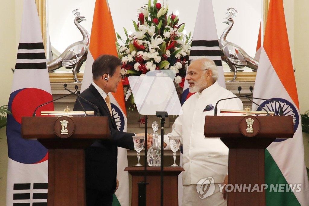 7月10日下午,韩国总统文在寅(左)和印度总理莫迪发布联合新闻稿前握手。(韩联社)