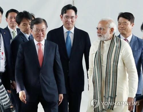 当地时间7月9日,在三星电子诺伊达工厂,韩国总统文在寅(左)和印度总理莫迪(右)在三星电子副会长李在镕(中)的陪同下出席工厂竣工仪式。(韩联社)