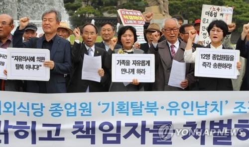 7月14日,在青瓦台附近,公民团体举行记者会,谴责朝鲜驻华餐厅弃朝投韩是被国家情报院诱引和绑架,要求严惩责任人。(韩联社)